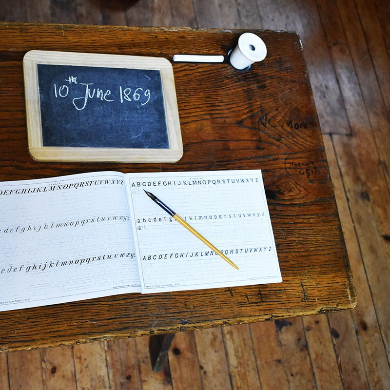 A school desk with slate and chalk and pen and ink.