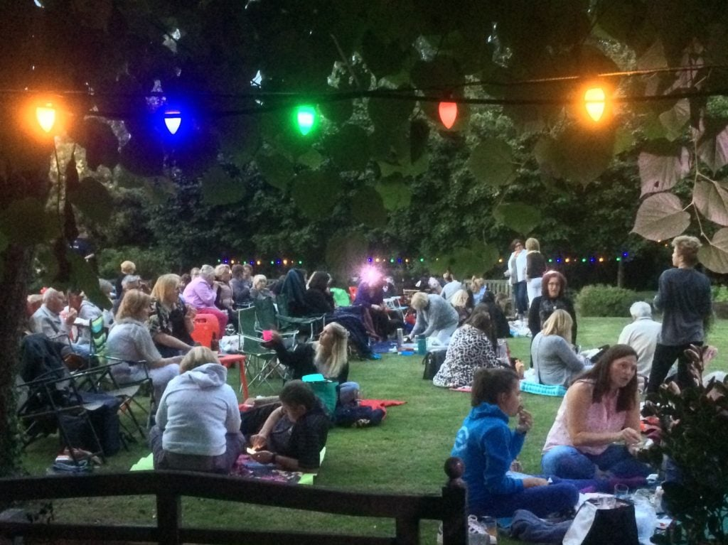 People picnicking on the lawn at Reveley Lodge during an open air film evening.