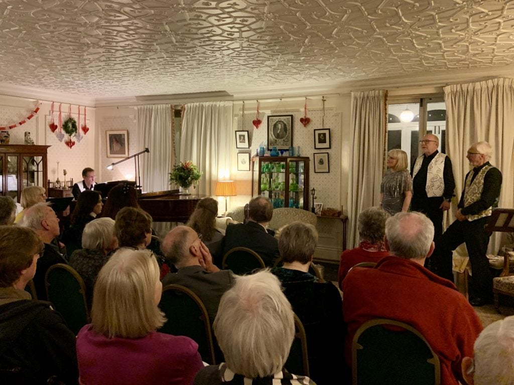 Local troupe the Bushey Waits performing in a Christmas parlour concert in the drawing room at Reveley Lodge.
